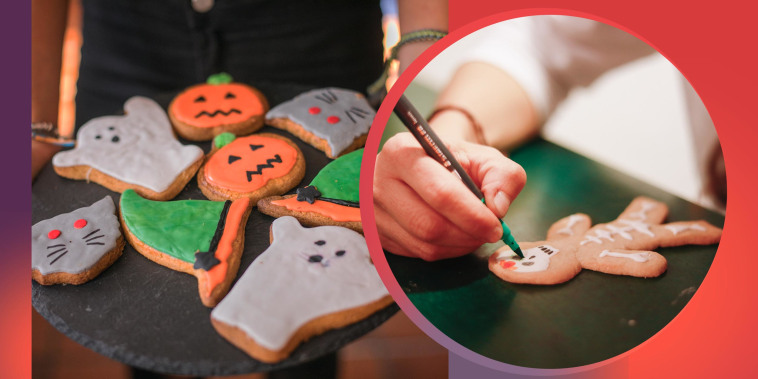 Someone holding a platter of halloween handmade cookies and a kid making skeleton