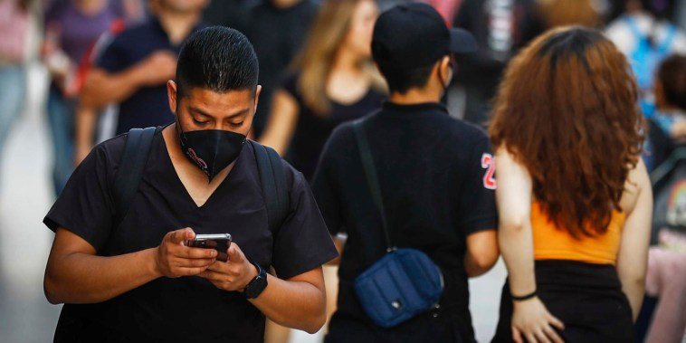 A man checks his phone in Mexico City on Oct. 4, 2021.