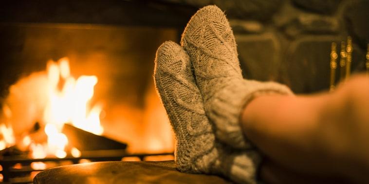 Feet in wool socks near fireplace