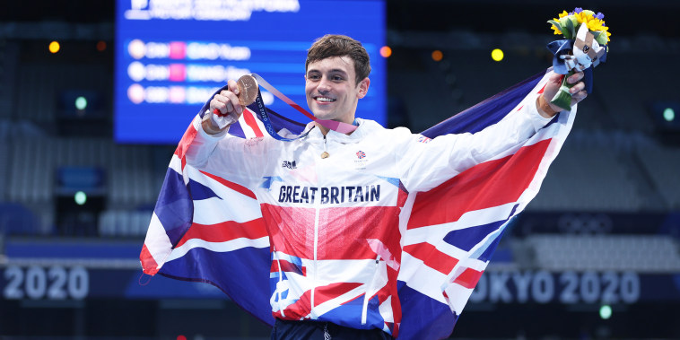 Tom Daley wears the flag of great britain and poses with his medal, smiling