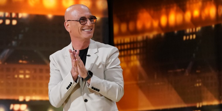 Howie Mandel claps in a white suit coat and circular glasses in front of a red and orange backdrop