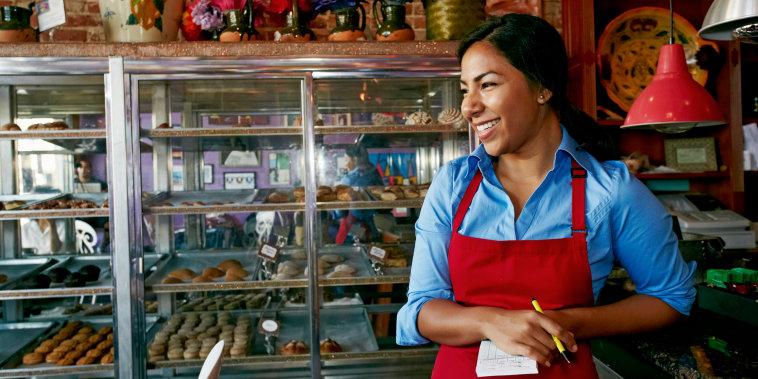 Hispanic waitress taking orders in bakery
