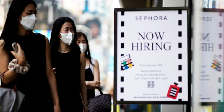 A sign advertising job openings is seen while people walk into the store in New York on Aug. 6, 2021.