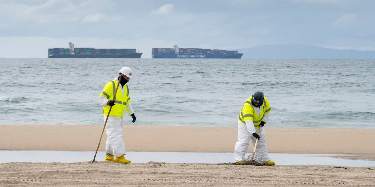 Image: Workers clean the sand south of the pier in Huntington Beach, Calif. on Oct. 8, 2021, after an undersea oil pipeline break off the Southern California coast.