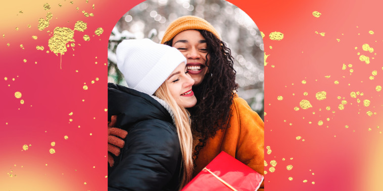 Happy girlfriends embracing holding Christmas gift by Christmas tree