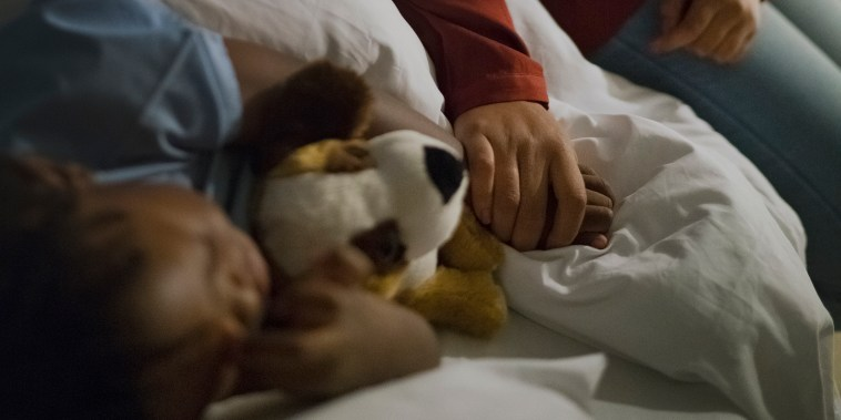 Mother holding ill son's hand sleeping on bed