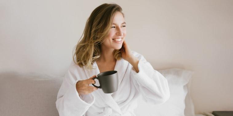 Woman wearing white bathrobe in bed holding a black mug