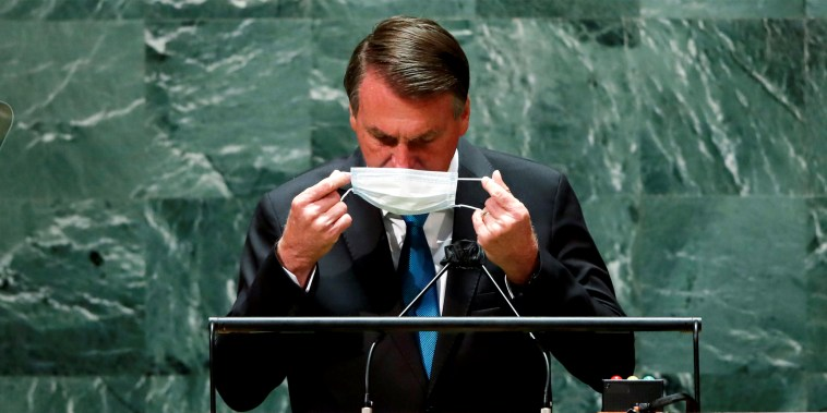 Image: Jair Bolsonoaro putting back his face mask after speaking.