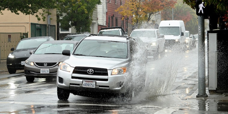 A car makes a big splash driving over a puddle on Third Street in San Rafael, Calif., on Oct. 21, 2021.