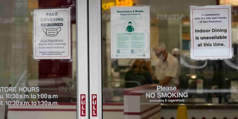 FILE - In this Oct. 20, 2021, file photo, signs advising vaccination and face mask requirements and no indoor dining are displayed on the door of an In-N-Out restaurant in San Francisco's Fisherman's Wharf. The restaurant's indoor dining was shut down this month by health authorities for not demanding proof of vaccination. (AP Photo/Jeff Chiu, File)
