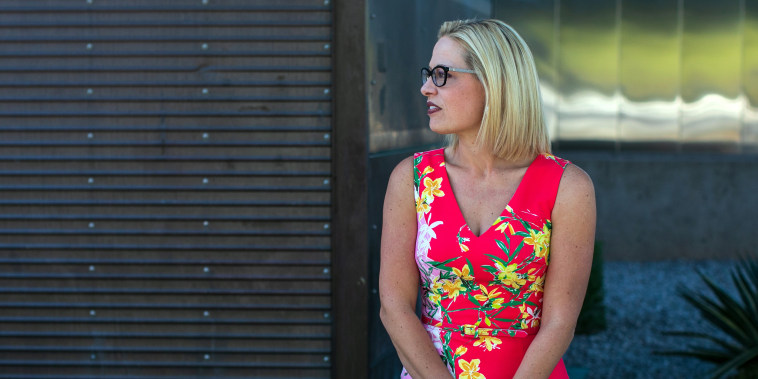 Rep. Kyrsten Sinema, D-Ariz., the Democratic candidate for the Senate, waits to greet voters at a polling place set up at the Burston Barr Central Library in Phoenix on Nov. 6, 2018.