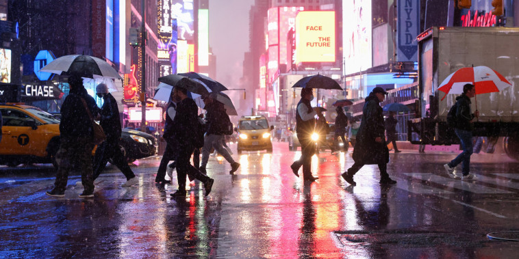 Image: People hold umbrellas while crossing the street during nor'easter in New York