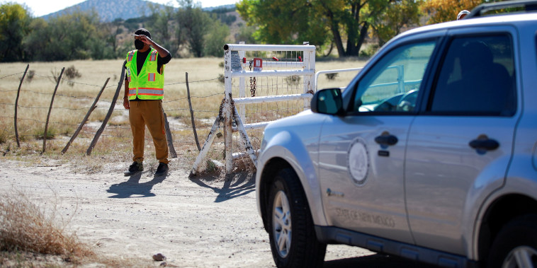 """Image: A security guard allows a compliance officer from the State of New Mexico onto the property of Bonanza Creek Ranch on the set of the movie \""""Rust\"""" in Santa Fe, New Mexico, on Oct. 22, 2021."""