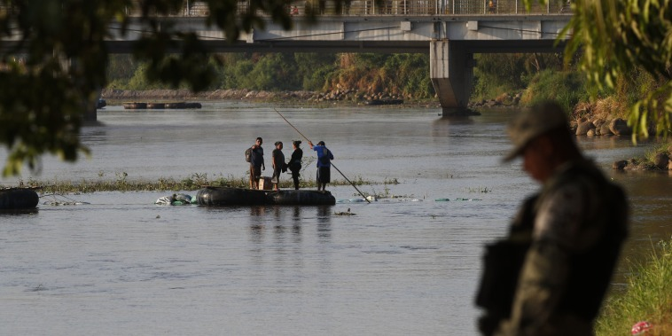 People travel across the Suchiate River from Guatemala to Mexico, as Mexican immigration agents enforce limits on all but essential travel at its shared border, near Ciudad Hidalgo, Mexico, on March 22, 2021.