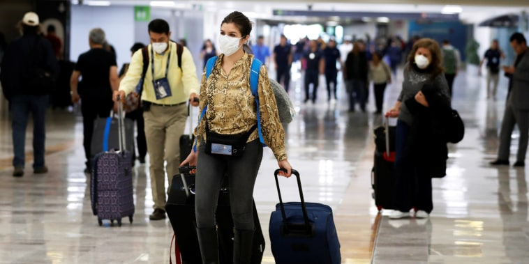 People walk in Benito Juarez International Airport in Mexico City on Feb. 28, 2020.