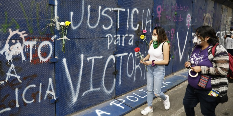 """Young women bring flowers to the perimeter wall of the Quintana Roo state offices sprayed with graffiti that reads in Spanish """"Justice for Victoria,"""" during a protest in Mexico City on March. 29, 2021."""