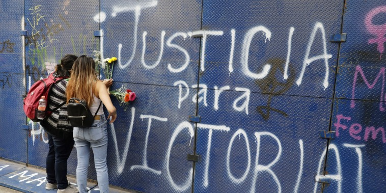 """Young women place flowers on the perimeter wall of the Quintana Roo state offices sprayed with graffiti that reads in Spanish """"Justice for Victoria,"""" during a protest in Mexico City, Monday, March. 29, 2021."""
