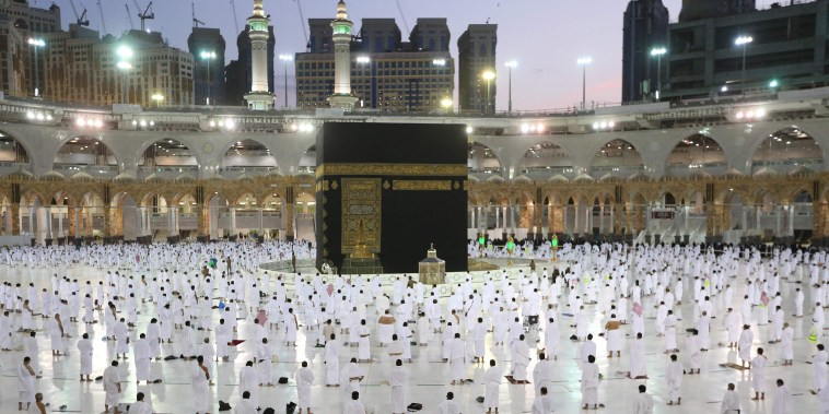 Image: Worshippers pray around the Kaaba, the holiest shrine in the Grand mosque complex in the Saudi city of Mecca during the first day of Ramadan on April 13, 2021.