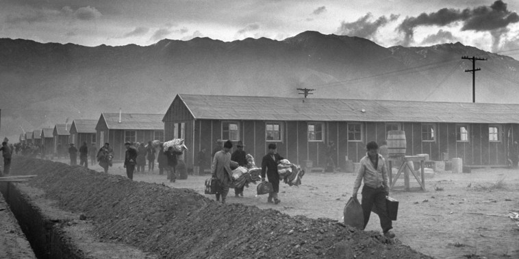 Image: The first group of 82 Japanese-Americans arrive at the Manzanar internment camp carrying their belongings in suitcases and bags, in Owens Valley, Calif., on March 21, 1942.