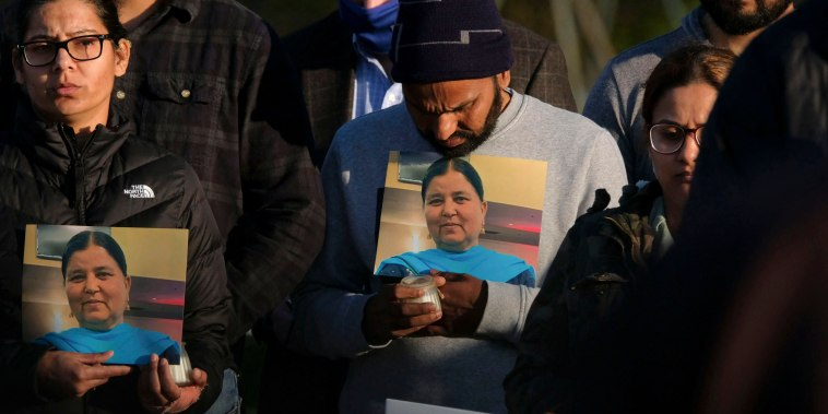 Image: Family members hold a photo of their loved one during a candlelight vigil in Krannert Park in Indianapolis on April 17, 2021, to remember the victims of a mass shooting at a FedEx facility.