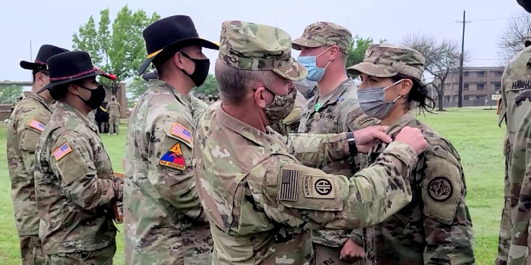 Fort Hood Command Sgt. Maj. Cliff Burgoyne, pins the Expert Infantry Badge, True Blue, on 1st Lt. Maria Eggers, from 1st Squadron, 3rd Cavalry Regiment, on April 16 at Fort Hood, Texas.