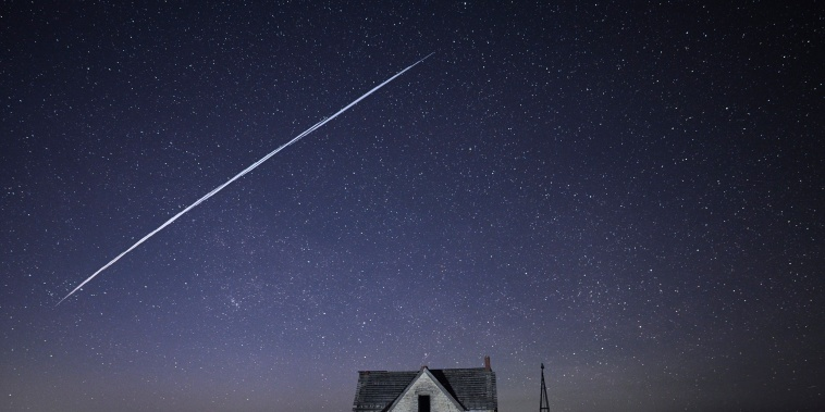 A string of SpaceX StarLink satellites passes over an old stone house near Florence, Kan., on May 6, 2021.