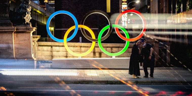 Image: A couple pose in front of the Olympic Rings in Tokyo's Nihonbashi district on July 10, 2021.