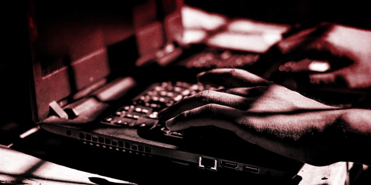 A persons hands on a laptop keyboard