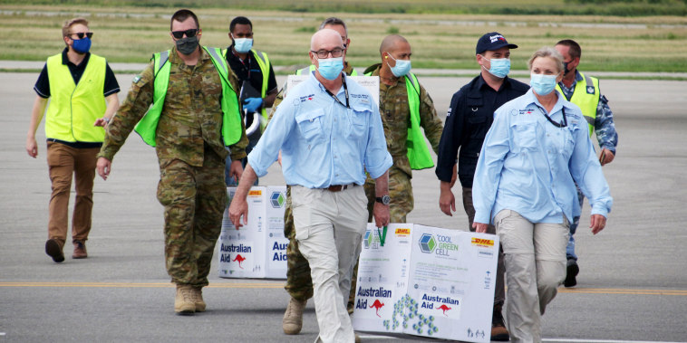 Inage: Australian officials carry boxes containing some 8,000 initial doses of the AstraZeneca vaccine,