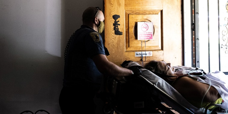 Image: A paramedic transports a woman suspected of experiencing a severe Covid-19 emergency on Sept. 6, 2021 in Louisville, Ky.