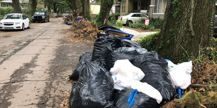 Image: Bags and containers of household garbage and piles of storm debris line a New Orleans street on Sept. 17, 2021.