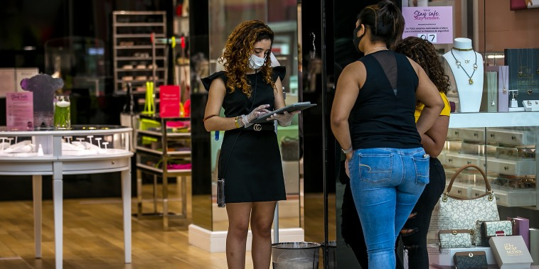 Image: An employee helps customers at the Mall of San Juan in Puerto Rico on June 1, 2020.