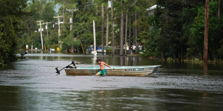 Image: A child walks a boat through floodwater Aug. 30, 2021 in Kiln, Mississippi. Tropical Storm Ida made landfall as a Category 4 hurricane in Louisiana and brought flooding and wind damage along the Gulf Coast.