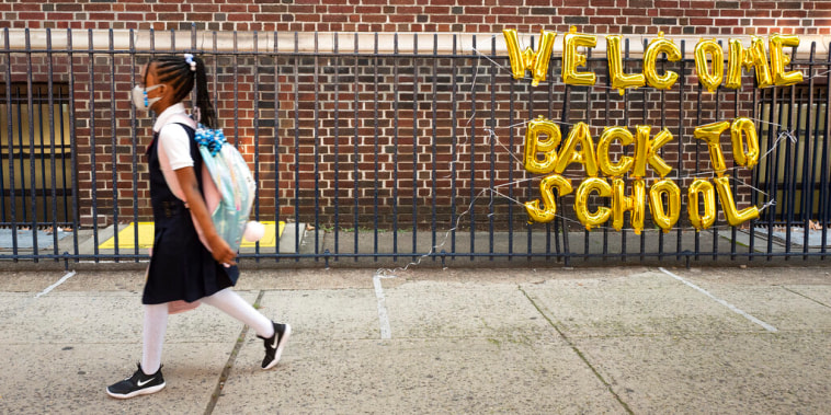Una niña pasa frente a un letrero de 'Bienvenido de vuelta a la escuela' en Brooklyn, Nueva York