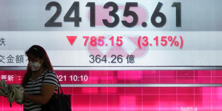 Una mujer pasa enfrente de una pantalla que muestra los índices de valores de la Bolsa de Hong Kong; el 20 de septiembre de 2021.