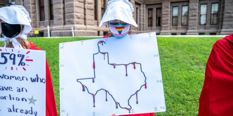 Una manifestante vestida de criada protesta frente al Capitolio en Texas en mayo.