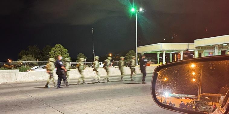 Agentes de la Oficina de Aduanas y Protección Fronteriza escoltan a soldados mexicanos detenidos tras cruzar la frontera e ingresar a Estados Unidos en el Puente Internacional Córdova de las Américas, en El Paso, Texas, el 25 de septiembre de 2021.