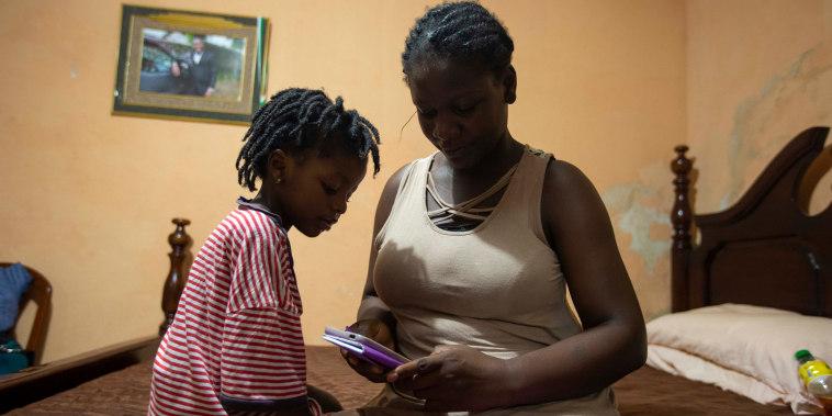 Deportados de EE.UU. un día antes, Delta de León y su hija Chloe, de 2 años, pasan tiempo en la casa de un familiar en Puerto Príncipe, Haití, el jueves 23 de septiembre de 2021.