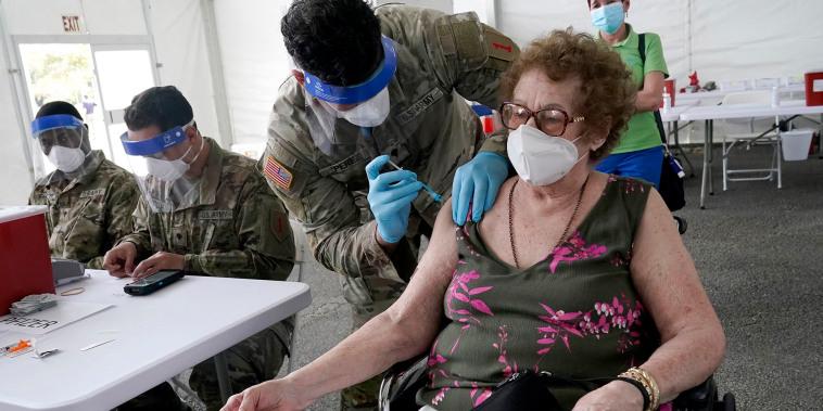 Loida Méndez, de 86 años, recibe la primera dosis de la vacuna COVID-19 de Pfizer de manos del médico del ejército estadounidense Luis Pérez, en un centro de vacunación de la FEMA en el Miami Dade College en North Miami, Florida.
