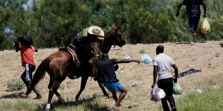 Un agente de la patrulla fronteriza estadounidense a caballo agarra la camisa de un migrante que intenta regresar a Estados Unidos a lo largo del Río Grande el 19 de septiembre.