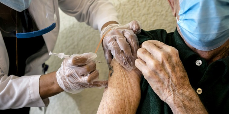 A resident receives a Pfizer-BioNtech Covid-19 vaccine from a healthcare worker at The Palace, an independent living community for seniors, at Coral Gables in Miami on Jan. 12, 2021.