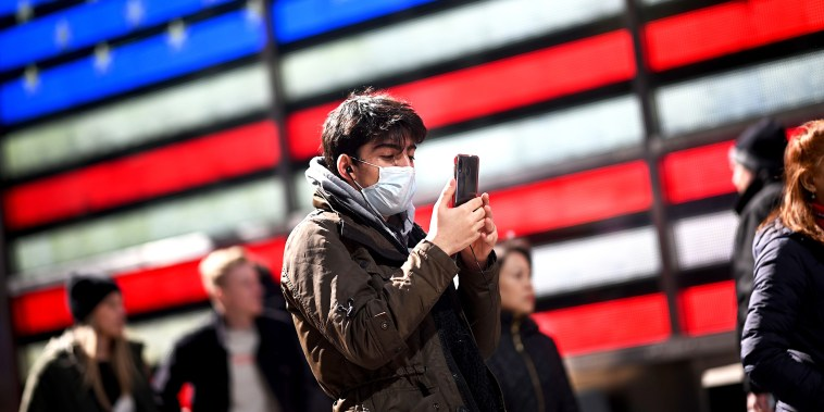 A man uses his cellphone at Times Square in N.Y., on March 5, 2020.