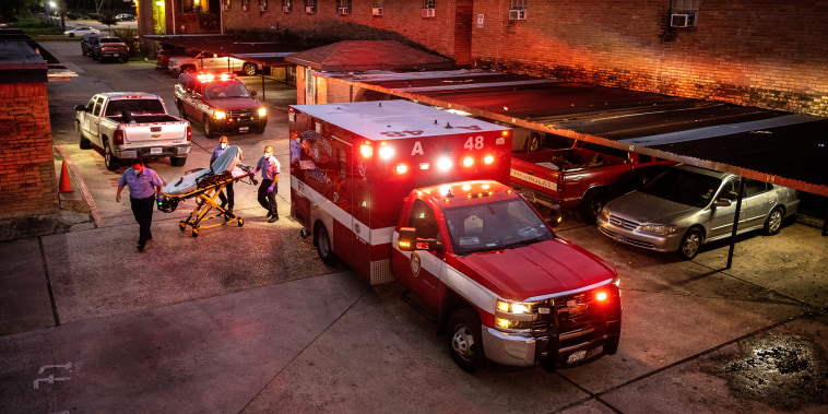Houston Fire Department paramedics prepare to transport a Covid-19 positive woman to a hospital on Sept. 15, 2021 in Houston, Texas.