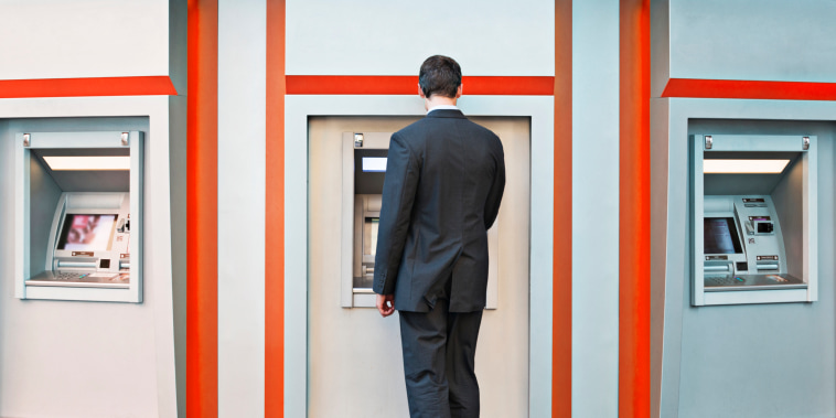 A person uses an ATM at a bank.