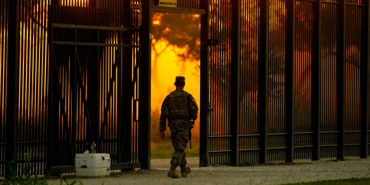 A National Guardsman stands guard at a fence that runs along the Rio Grande near the International bridge on Sept. 17, 2021, in Del Rio, Texas.