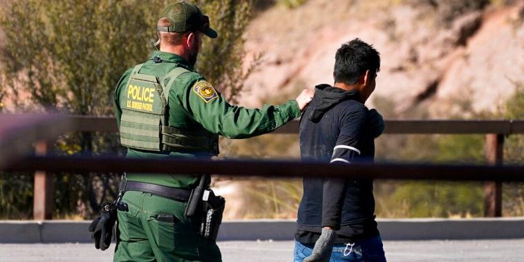 Un agente fronterizo camina detrás de un migrante interceptado en Arizona el 9 de diciembre de 2020.