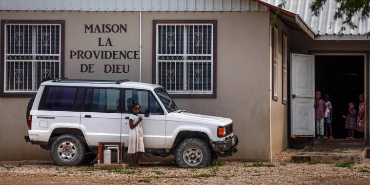 Varios niños de pie frente a la entrada de la sede de la misión cristiana 'Maison La Providence de Dieu', a la que pertenecen las 17 personas que fueron secuestradas por una pandilla en Puerto Príncipe, Haití