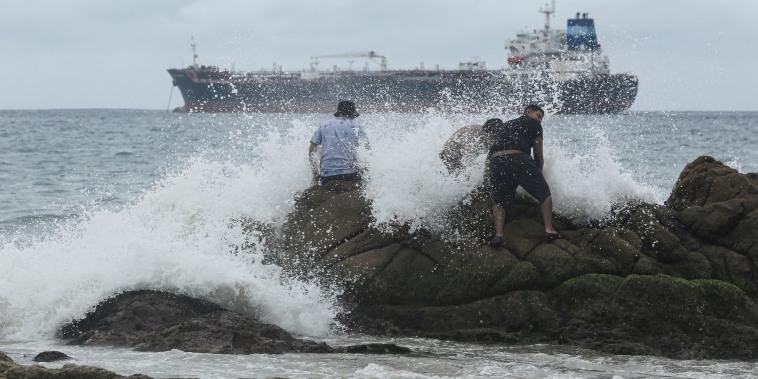 Un grupo de gente en una playa mientras el fenómeno Rick se convierte en huracán frente a la costa del Pacífico de México, en Acapulco, México, el 23 de octubre de 2021.