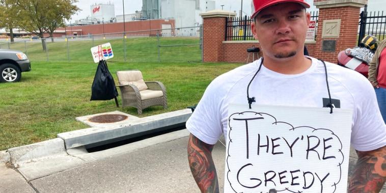 """Michael Shlee, trabajador de la planta de cereales de Kellogg's, hace huelga frente a la entrada principal de la fábrica el miércoles 6 de octubre de 2021, en Omaha, Nebraska. En su letrero se lee: """"son avariciosos"""""""