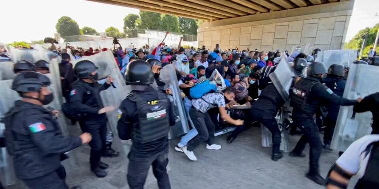 Un grupo de inmigrantes rompe una primer barricada de la policía este sábado 23 de octubre en Tapachula, México, para avanzar hacia el norte. Su objetivo es llegar a Estados Unidos.
